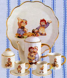 Porcelain mini tea set.  Includes teapot with lid, covered sugar bowl, creamer, two cups with saucers and serving platter.