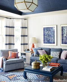 Blue living room with grasscloth wallpaper on the ceiling, patterned area rug, striped curtains and colorful accent pillows.