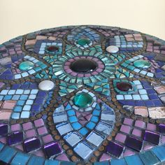 A beautiful mandala mosaic panel. This is an original, one-of-a-kind piece of art. I used a mixture of purple, blue and teal tiles in both a matte and gloss finish. Ceramic copper speckled dots accentuate the petals, and a mix of moonshine glass tiles add that finishing sparkle! The base is made from MDF and hand painted on the back and sides to finish. Diameter: 30cm (12in) Depth: 1cm This item is intended for indoor use only. It would look lovely hung on a wall or displayed on a stand i...