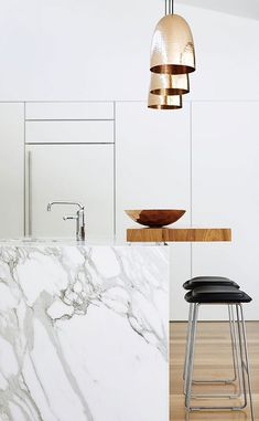 White marble kitchen island with black bar stools and gold pendant lights