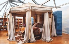 I love how the heavy draping and canopy creates a sense of cosiness and security in place of the glass ceiling.