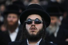 An ultra-Orthodox Jew uses binoculars during a celebration marking the end of a seven-year cycle of studying texts from the Talmud in Jerusalem.