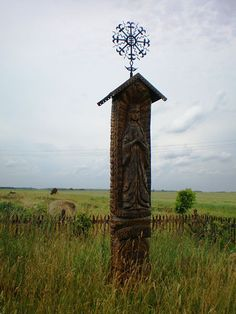 Prechristian Baltic Sun and the Moon cross at the top of wooden monument. Christian and pagan traditions are very interwined in Lithuanian culture