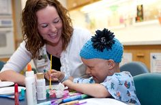 """""""Delivering a special kind of care."""" Child Life Specialist Rachel Niensteadt shares a laugh with one of the young patients at University of Iowa Children's Hospital."""