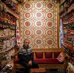 Adem Sad'c poses for a photograph at his store selling traditional rugs and fabrics