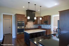 Pendant lights help to soften the mood in this #kitchen.The Foxglove #1297. http://www.dongardner.com/house-plan/1297/the-foxglove. #HomePlan #HouseDesign