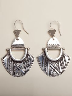 Make a bold statement with these stunning Tuareg hinged shield earrings. Crafted from 99.9% pure silver, Elhadji and the Koumama family collective of silversmiths in Agadez Niger use simple tools like