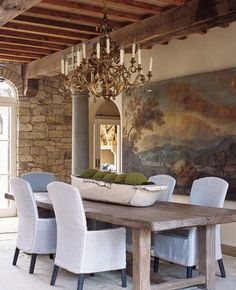 An antique gilded wood chandelier casts a soft glow on an 18th century Umbrian painting by Carlo Labruzzi and French farmhouse table