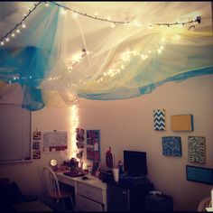 This is suuuuuch an awesome idea. Christmas lights then really light, see-through fabric hanging below on the ceiling.