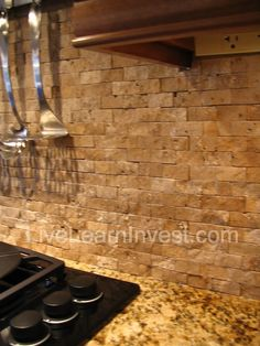 Coastal kitchen remodel with travertine tile backsplash dark
