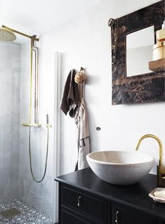 a worn metal framed mirror adds a rough edge to the clean lines of the marble sink + shower