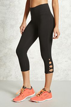 8ca94472cffe22 A pair of stretch-knit capri leggings featuring a crisscross cutout hem  detail and an