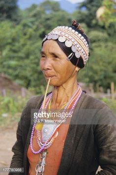 Thailand, Akha village near Ching Mai, close-up sideview of native woman with pipe in mouth.