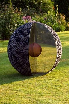 The Kernel - a black stone garden sphere with a slice cut out, revealing a stainless steel facade and a patinated kernal