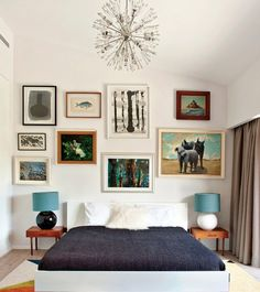 eclectic mix of paintings in mid-century bedroom