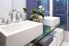 """A designer de interiores Simone Bigoto preferiu a bancada de vidro (2 x 0,50 m) para este ambiente, pois """"o vidro é ótimo para uso em áreas molhadas e úmidas. Além disso, o tipo incolor proporciona transparência e leveza ao ambiente"""". Pastilhas de vidro emolduram os espelhos e as paredes internas, """"contrastando com as demais,  que têm pintura epóxi branca, e criando um efeito agradável aos olhos, setorizando as áreas do banheiro"""", completa a profissional."""