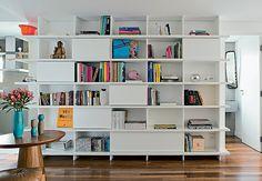 Para ligar os ambientes desde a cozinha até a sala de estar, a estante de laca branca, desenhada pela SAO Arquitetura, envolve o volume onde fica o lavabo