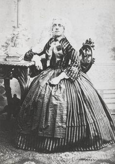 Vrouw in streekdracht uit Beijerland. De vrouw draagt onder de sluiermuts een oorijzer met krullen aan de uiteinden. Aan de krullen hangen oorijzerhangers. ca 1865 #HoekseWaard #ZuidHolland