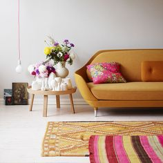 elle blomster - such a beautiful mustard couch. Use of analogous colors with couch, like pinks and yellows. Would go just as well with blues and some greens.