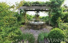 A grape-covered pergola shields an antique millstone table, essentially creating an outdoor dining room in this seaside Nantucket garden. See more great outdoor spaces.