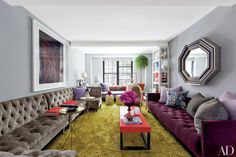 In the New York City living room of stylist Carlos Mota, the walls are painted in Donald Kaufman's DKC-7. A bespoke button-tufted sectional and low-back sofa frame the space, which also includes a lacquer cocktail table of Mota's own design and a pair of Jean-Michel Frank gueridons; the large-scale photograph is by Todd Eberle, and the silk carpet is by Carini Lang.