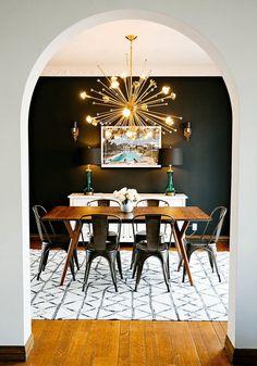 modern dining room interior with industrial metal chairs, dark bronze metal chairs, starburst chandelier, black and white tribal rug, dark accent wall, sherwin williams sealskin, dark bronze, dark brown