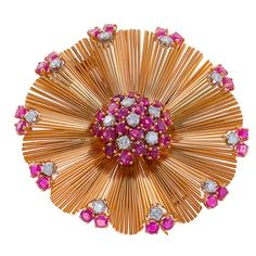 18 karat gold brooch centers a round rubies and diamonds in a floral motif, surrounded by undulating gold wires ending in prong-set round rubies and diamonds. Total diamond @ 1.60 carats, ruby @ 8.0 carats. The brooch measures 2 1/4 inches wide. And it is gorgeous! (cost: 6500.)