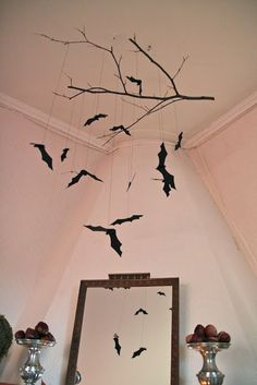 DIY bat mobile using a spray-painted black branch, fishing line & construction paper bats. Easy, cheap but effective! #halloweendecorations #diypartydecorationsvintage