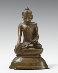 A Burmese bronze figure of a Lotus Buddha Shakyamuni. 18th century  A Burmese bronze figure of a Lotus Buddha seated in paryankasana on a lotus above a pedestal with an engraved inscription, the right hand in bhumisparsha mudra, a myrobalan fruit in his left hand, the head is covered by lotus petals instead of the usual hair curls. 18th century.  Height 20.5 cm