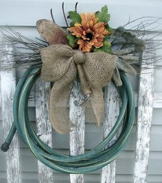 garden hose wreath....wrap an old garden hose into circular form, secure with wire, add burlap bow and silk sunflower!