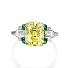 Vivid Yellow diamond weighing carats, flanked by six baguette and bullet-shaped diamonds weighing approximately carat, further accented by eight calibré-cut emeralds, size circa Canary Diamond, Yellow Diamond Rings, Vintage Diamond Rings, Diamond Jewelry, Emerald Rings, Ruby Rings, Or Antique, Antique Jewelry, Vintage Jewellery