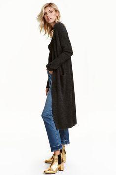 Gilet en maille: Gilet long en maille souple enrichie d'une touche de laine. Modèle avec parties côtelées et poches devant. Couture d'épaule descendue et manches longues. Sans boutonnage.