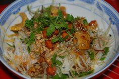 Con Hen is served with a little rice and a lot of vegetables, herbs and fruit, add clams in the center, top with fried pork fat, roasted pea...