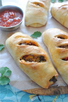 Southwest Breakfast Stromboli Recipe ~ Says: Basically what's happening here is a conglomeration of transglobal flavor attacks. We've got the Southwest flair with the seasoned scrambled eggs, freshly diced red pepper and punchy cilantro. We've got the Italian spirit with the fluffy, stretchy fresh pizza dough. We've got the down home comfort charm with spicy country sausage and extra-sharp cheddar cheese. All rolled up into a million little pockets of frickin' glory!