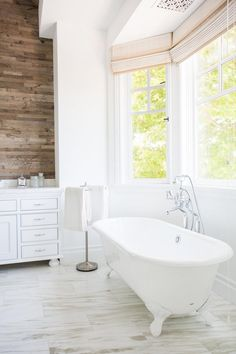 An elegant clawfoot tub brings a classic, traditional element to this luxurious master bathroom. The tub is tucked in a large bay window that floods the entire space with loads of natural light. Clawfoot Tub Bathroom, Bathroom Spa, Master Bathroom, Bathroom Lighting, Bathroom Ideas, Bathroom Images, White Bathroom, Bathroom Designs, Bathroom Inspiration