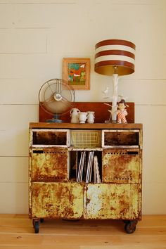 A rolling metal storage unit sits below one of Kelley's framed paintings. A vintage fan cools the room.