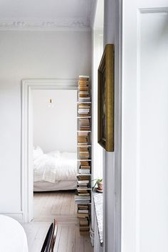 tall stack of books in white hallway / sfgirlbybay