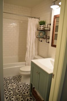 Our small bathroom remodel. Subway tile walls, Merola Tile Arte Gray cement tile look floors and Annie Sloan Duck Egg Blue vanity.