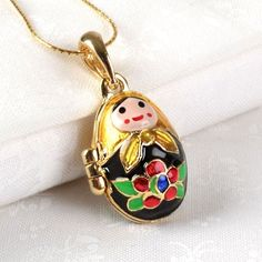 """#Matryoshka Locket Pendant - $84.99 How cute! This Faberge style, egg shaped locket of a nesting doll holding another smaller doll, is crafted so that you can keep the tiny doll inside the """"mother"""" or let it dangle out the tiny hole at the bottom of the locket.  From the top of the bail to the bottom of the mini matryoshka, this piece of jewelry is about 2"""" long. The #Russian doll design is on both sides of the locket. The chain is not included. #necklace"""