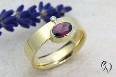 An oval red tourmaline is followed by a smooth polished 750/-er yellow gold gold ring side. A footbridge across the ring with a small brilliant-cut diamonds in a yellow gold combines the tourmaline. The ring is about 6 mm wide, the tourmaline has a size of 7 x 5 mm, since