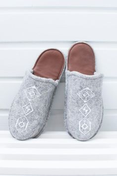 Finnish design  These slippers will keep your feet warm even over the coldest times.   Tossutellen products have been made of 100% wool felt and reindeer leather.   As a material wool is warm when you need it and cool when it's hot outside. Wool is non-sweaty and it rejects dirt. The softness of the slippers makes your feet happier than ever. The bottom of the slipper is reindeer leather, so the slippers are not slippery against the floor. Leather is also an excellent heat insulator. Felted Slippers, Leather Slippers, Textile Products, Shoe Size Conversion, Designing Women, Wool Felt, Reindeer, Patches, Footwear
