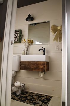 industrial style bathroom with planked walls and DIY floating reclaimed wood vanity - Girl Meets Carpenter featured on @Remodelaholic