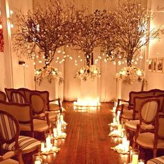 Dramatic trees, white flowers and a sea of candles create a beautifully warm and intimate setting for this wedding ceremony. McCalls Catering and Events.