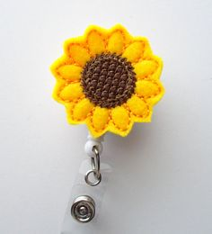 This retractable ID felt badge holder features a sunflower felt applique. Sits on a white, hard plastic badge reel.  Applique measures 1.5. Cord extends to 24.  Click here to view my other felt badge holders: https://www.etsy.com/shop/BadgeShack?section_id=13478374  ************************************************************  Comes from a smoke free home.  ************************************************************  Have a custom order? Just send me a message and I will make anything to…