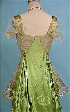 Back view, detail - 1916 Evening Gown of Apple Green Chinese Silk Damask Dramatically Draped over Gold Lame Lace over Gold Lame Lining. Nearly invisible chiffon covers the bodice and sleeves. Remarkable green stones hold up the silk pieces front and back and at gold lame straps. One little velvet flower decoration at bust.