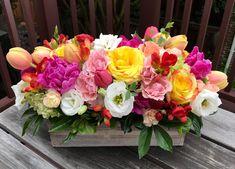 Flower box with spring flowers: tulips, ranunculus, lisianthus, ruffled roses, peonies