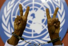 An anti-government protester flashes the victory sign in front of the United Nations building in Manama, Bahrain. Opposition activists staged a rally outside the U.N. office, demanding freedom for prisoners and democracy in the Gulf kingdom.