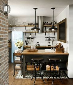 Baby blue Smeg - exposed brick wall - open shelving - industrial lights - industrial kitchen island