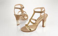 Sandalette mit Ziernieten und verstellbarem Fesselriemchen. Absatz mit goldfarbener Plakette.