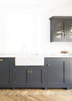 Navy kitchen cabinets with white walls, counters, and sink. Navy kitchen cabinets with white walls, counters, and sink. Navy Blue Kitchen Cabinets, Shaker Style Kitchen Cabinets, Shaker Style Kitchens, Kitchen Cabinet Styles, Kitchen Cupboards, New Kitchen, Home Kitchens, Kitchen Decor, Devol Kitchens